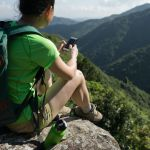 Hiking using mobile phone on cliff edge