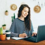 Positive pretty woman with long hair at home office at work desk works. Remote business.